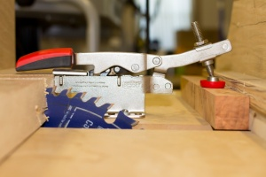 Bessey auto adjust clamp holding down a pen blank on the table saw crosscut sled.